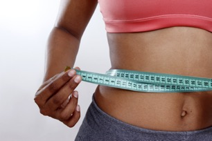 Person measuring their waist after CoolSculpting