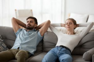 Man and woman sitting on the couch after eating a big meal