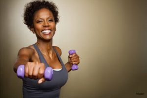 Woman working out while hold purple weights
