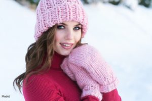 Woman wearing a pink hat in mittens in the snow
