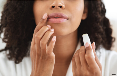 Woman putting on lip balm