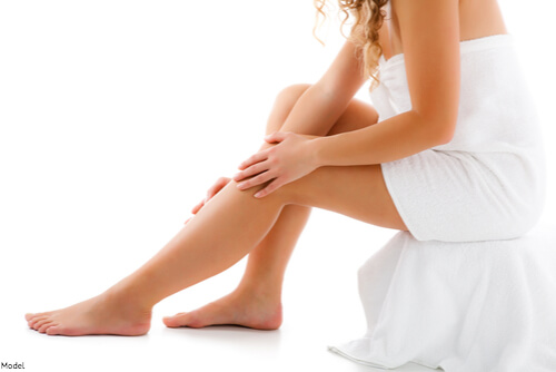 Woman touching her smooth legs thanks to laser hair removal